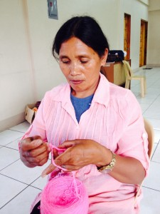 Manang Leonila tries on the new skill she has learned from one of the SLP trainings she has attended. Knitting would help her produce new products which she can sell.