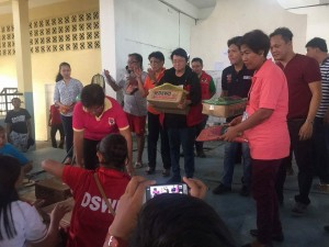 Department of Social Welfare and Development (DSWD) Secretary Judy Taguiwalo (4th from left) and Tuguegarao City Mayor Jefferson Soriano (5th from left) distribute food packs to the displaced families staying inside the Tuguegarao People's Gym to show that an efficient disaster relief operations need the joint effort of the National Government and the Local Government Units.